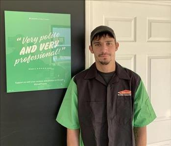 A man in a SERVPRO uniform is standing in front of a SERVPRO banner with a positive google review on it.