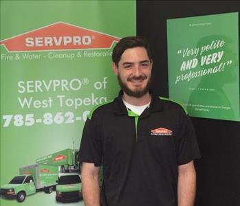 A male SERVPRO employee is standing in front of a SERVPRO sign.