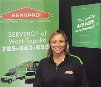 A female SERVPRO employee is standing in front of a SERVPRO sign.