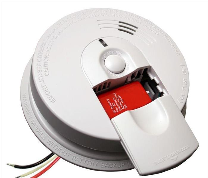A smoke detector with the slot to put the battery in open so you can see the battery